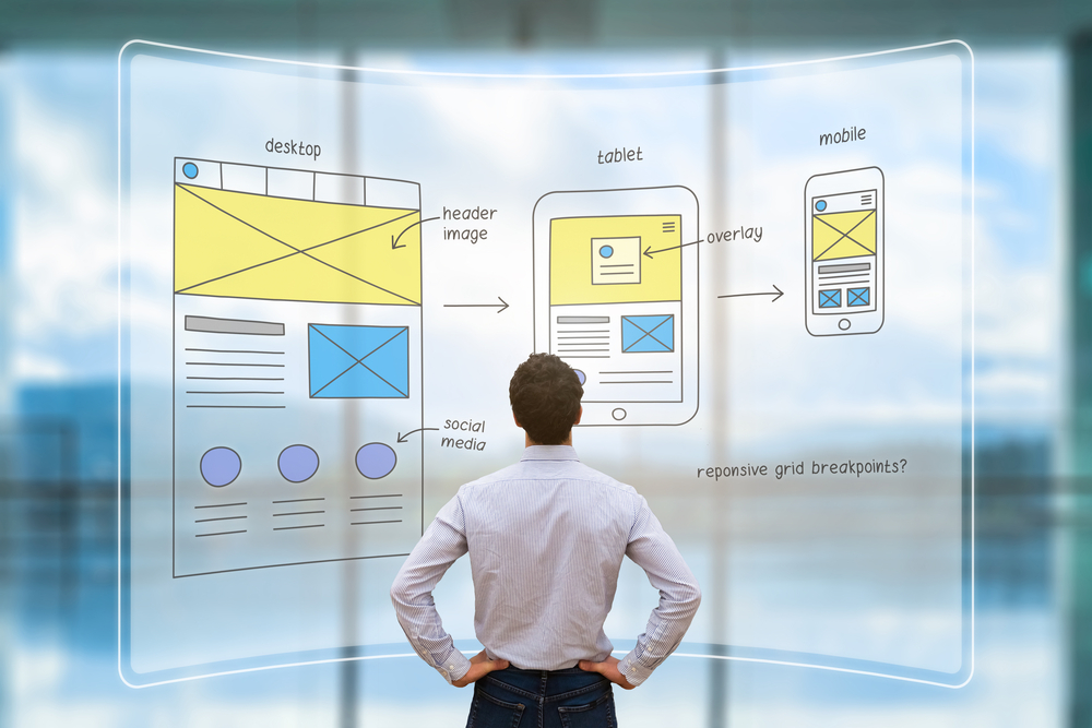 Website development UIUX front end designer reviewing sketched wireframe layout design mockup for responsive web content with AR screen
